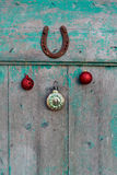 Old rusty horseshoe, Christmas toys and vintage clock on wooden door Stock Image