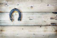 Old rusty horseshoe is hanging on a nail Stock Image