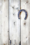 Old rusty horseshoe is hanging on a wooden background Royalty Free Stock Image