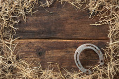 Old rusty horseshoe. Surrounded by straw on vintage wooden board Royalty Free Stock Photos