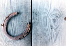 Old rusty horseshoe on vintage wooden board Stock Images