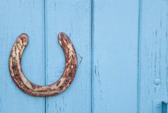 Old rusty horseshoe on wooden blue background. Stock Photos