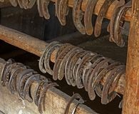 Old rusty,horseshoes. Aged rusty horseshoes hanging in the barn on a wooden rack Royalty Free Stock Images