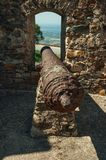 Old rusty iron cannon aiming through window in stone wall. Close-up of old rusty iron cannon aiming through window in the stone outer wall, in a sunny day at royalty free stock photography