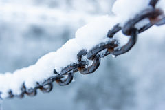 Old rusty iron chain on a frost covered with snow Royalty Free Stock Photo