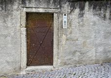 Old rusty iron door with modern intercom. At a house-wall, Bruneck, South Tyrol, Italy Stock Photography