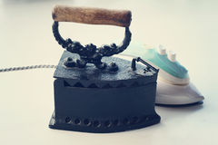 Old rusty  iron and modern new electric iron. Vintage image Royalty Free Stock Photography