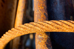 Old rusty iron rope against metal armature Stock Photos