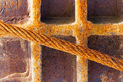 Old rusty iron rope against metal wall Stock Photography