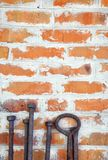 Old rusty iron scrap standing on the background of a brick wall. For your design royalty free stock images