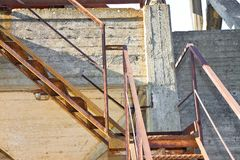 Old rusty iron staircase against a damaged concrete wall.  royalty free stock image