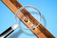 Old rusty iron structure with bolted metal profiles against a blue sky - Concept image seen through a magnifying glass.  royalty free stock images