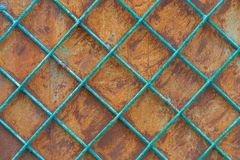 Old rusty iron wall behind a metal painted lattice stock photography