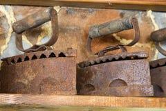 Old rusty irons on shelf. Retro domestic tools. Vintage irons. Rusty smoothing irons. Old rusty irons on shelf. Retro domestic tools. Vintage irons. Ancient stock photos