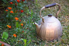 Old rusty kettle on grass Stock Photo