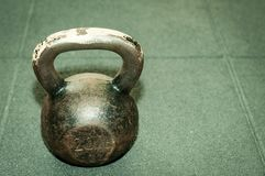 Old rusty kettlebell weight on the black gym floor with selective focus and film grain. Old rusty and heavy kettlebell weight on the black gym floor with stock image