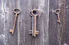 Old rusty key on farm barn wooden wall Royalty Free Stock Photos