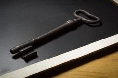 Old rusty key. On a black slate Stock Photography