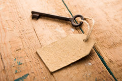 Old rusty key with a paper label on the wooden board Stock Photo
