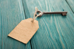 Old rusty key with a paper label on the wooden board Stock Photos