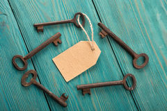 Old rusty key with a paper label on the wooden board Stock Images