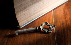 Old rusty key with part of antique book. Royalty Free Stock Images