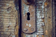 Old rusty keyhole in the old wooden door royalty free stock photography