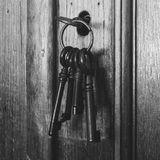 Old rusty keys inside a keyhole of an old antique closet. vintage design black and white. Old rusty keys inside a keyhole of an old antique closet. vintage royalty free stock image