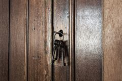 Old rusty keys inside a keyhole of an old antique closet. vintage design. Close-up stock photo