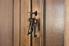 Old rusty keys inside a keyhole of an old antique closet. vintage design. Close-up stock images