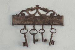 Old rusty keys. Hang on a figured metal bar with hooks Royalty Free Stock Photo