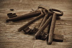 Old and rusty keys. Some old and rusty keys on a rustic wooden table Royalty Free Stock Photography