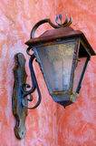 Old rusty lantern. On the colorful stucco wall royalty free stock photo
