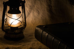 Old rusty lantern and a book Royalty Free Stock Photo