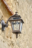Old rusty lantern. On the wall Royalty Free Stock Photography