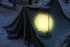 Old rusty Lighted lantern shining bright light during night, Miner camp, Survival hike in nature by night stock photos