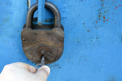Old rusty lock with a key on a blue background Stock Photos