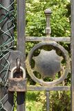 Old rusty lock on a metal gate into the garden. Lock on the iron gate. Symbol imprisonment and slavery. Property security chain Royalty Free Stock Image