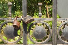 Old rusty lock on a metal gate into the garden. Lock on the iron gate. Symbol imprisonment and slavery. Property security chain Royalty Free Stock Images