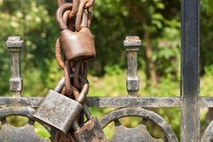 Old rusty lock on a metal gate into the garden. Lock on the iron gate. Symbol imprisonment and slavery. Property security chain. Closed iron gate with a lock Stock Photos
