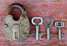 Old rusty lock with three different keys on wooden surface Royalty Free Stock Photos