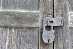 Old and rusty  lock on wooden door of an abandoned house Royalty Free Stock Images