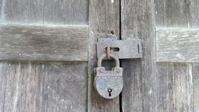 Old and rusty  lock on wooden door of an old abandoned house Royalty Free Stock Photography
