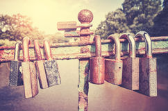 Old rusty love padlocks on a bridge. Retro stylized picture of old rusty padlocks on a bridge, love symbol, shallow depth of field Royalty Free Stock Photos