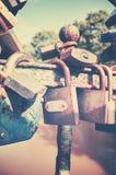 Old rusty love padlocks on a bridge. Retro stylized picture of old rusty padlocks on a bridge, love symbol, shallow depth of field Royalty Free Stock Photography