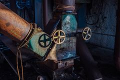 Old rusty machine valves of pipeline at abandoned factory royalty free stock image