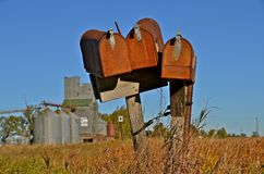 Old Rusty Mailboxes. Three rusty old mailboxes stand unused as is the rural elevator in the background Royalty Free Stock Image