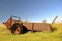 Old rusty manure spreader with fall foliage Royalty Free Stock Images