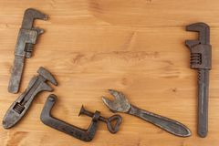 Old rusty mechanics tools on a wooden background. Advertising for new tools. Sales tools Stock Images