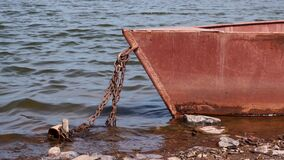 Old rusty metal boat chained on a river bank on sunny day